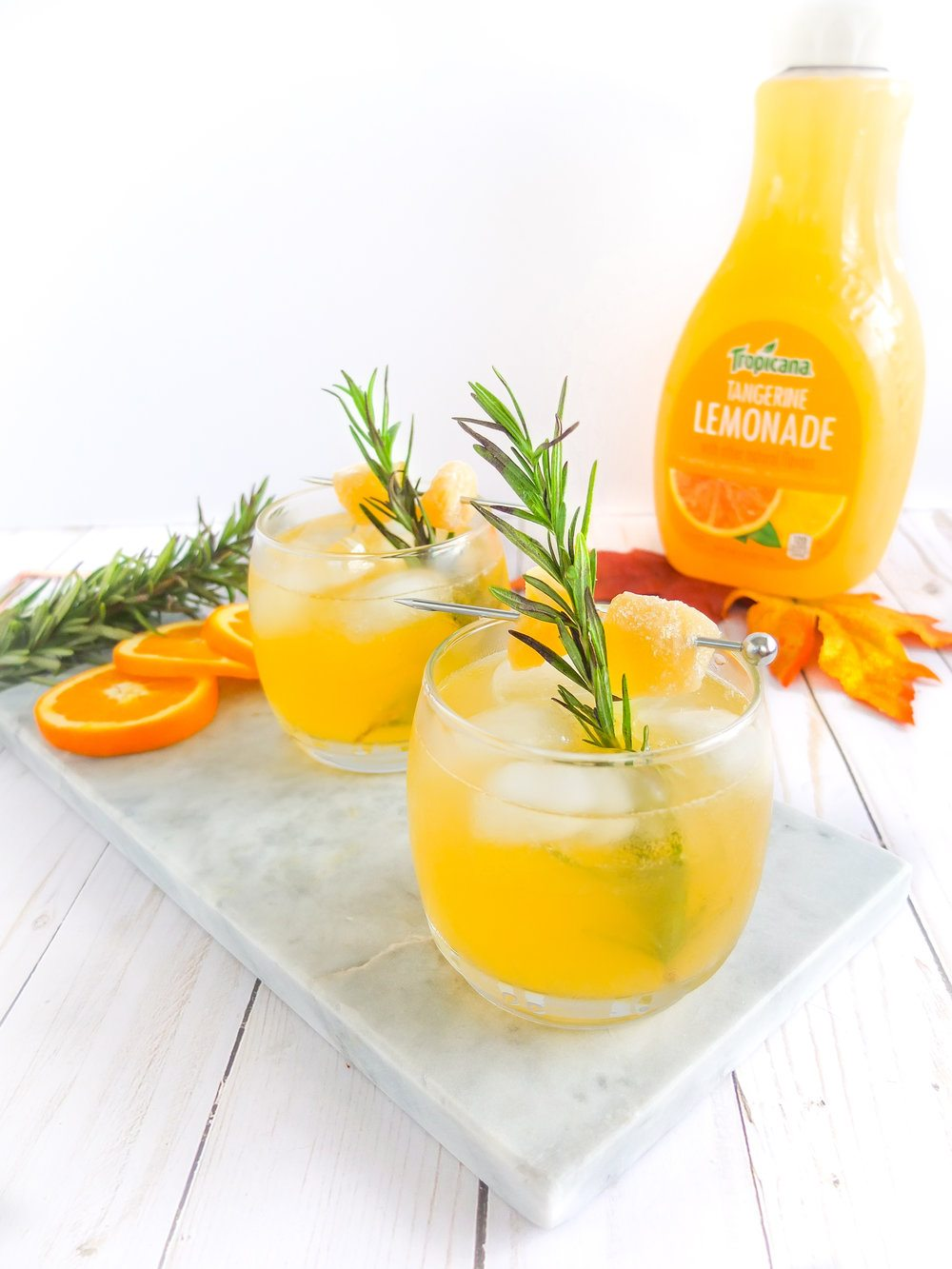 Easy, low ingredient fall bourbon cocktail. This easy autumn cocktail is made with bourbon, Tropicana Tangerine Lemonade, and ginger rosemary syrup. It's a spicy, sweet, and delicious fall cocktail. Also learn how to make ginger rosemary syrup. Perfect for fall gatherings, fall hosting, fall recipes, and fall drinking. MSG 4 21+ #ad #MixedWithTrop // www.elletalk.com