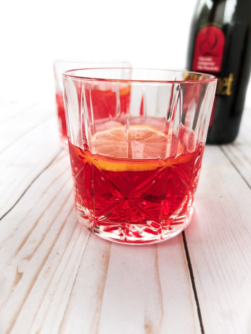 A cocktail perfect for The Crown viewing party. It is said that The Queen of England's favorite cocktail is a Dubonnet and Gin. It's an easy gin three ingredient cocktail of dubonnet, gin, and a lemon wedge. A delicious pre-dinner aperitif or just for sipping. Queen Elizabeth II's Dubonnet and Gin. www.elletalk.com // #TheCrown #Cocktail #CocktailRecipe #WatchParty #QueenElizabeth #QueenofEngland #HRM
