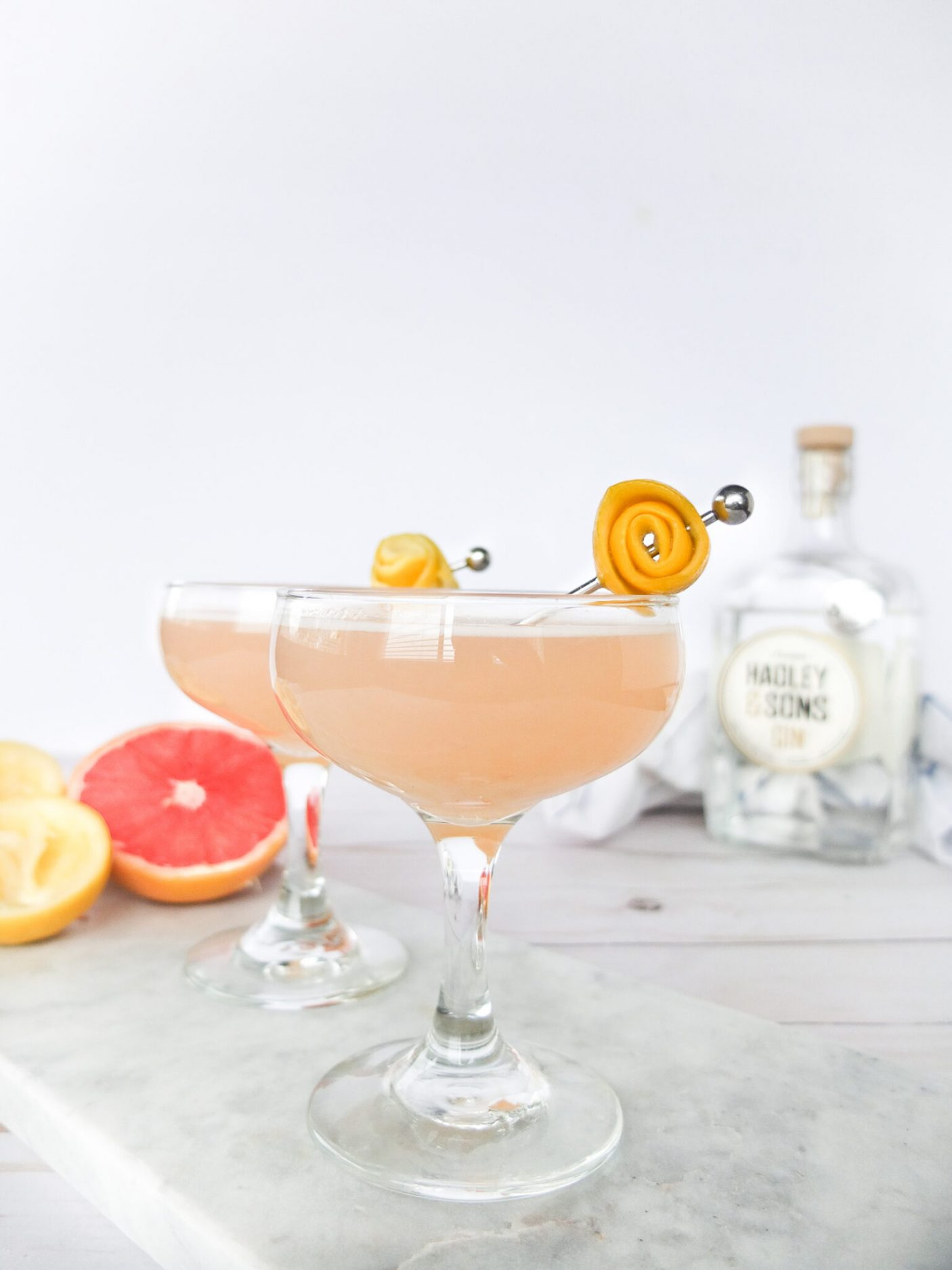 A bright and delicious winter cocktail using grapefruit and lemon to make a winter gin sour cocktail. This cocktail recipe uses winter citruses to make a sour gin cocktail. Perfect for winter sipping and works well in the summer for a light and refreshing drink. Served in a coupe glass.