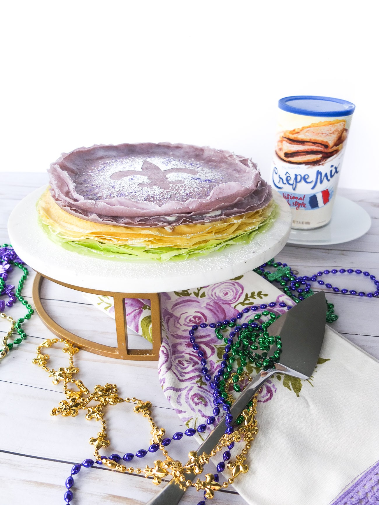 A twist on a Mardi Gras recipe classic takes layers of crepes and praline cream cheese frosting to make a King Cake inspired Crepe Cake. This Crepe King Cake is perfect if your looking for a unique Mardi Gras food or need a dessert to entertain for a Mardi Gras party. #ad #mardigras #mardigrasfood #worldmarket @worldmarket #crepe #crepecake #dessert