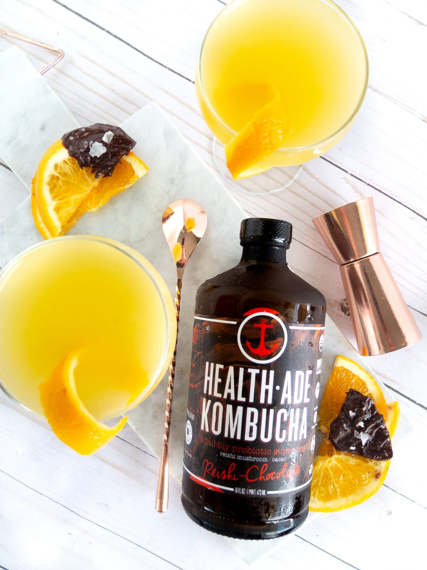 This Choc Orange Fizz is a kombucha cocktail that is the perfect balance of orange and chocolate for a healthier cocktail option. This dreamy drink is sweet, tart, and a whole lot of bubbly with Health-Ade Kombucha's Reishi-Chocolate. Elle Talk #kombucha #kombuchacocktail #cocktail #cocktails #cocktailrecipe