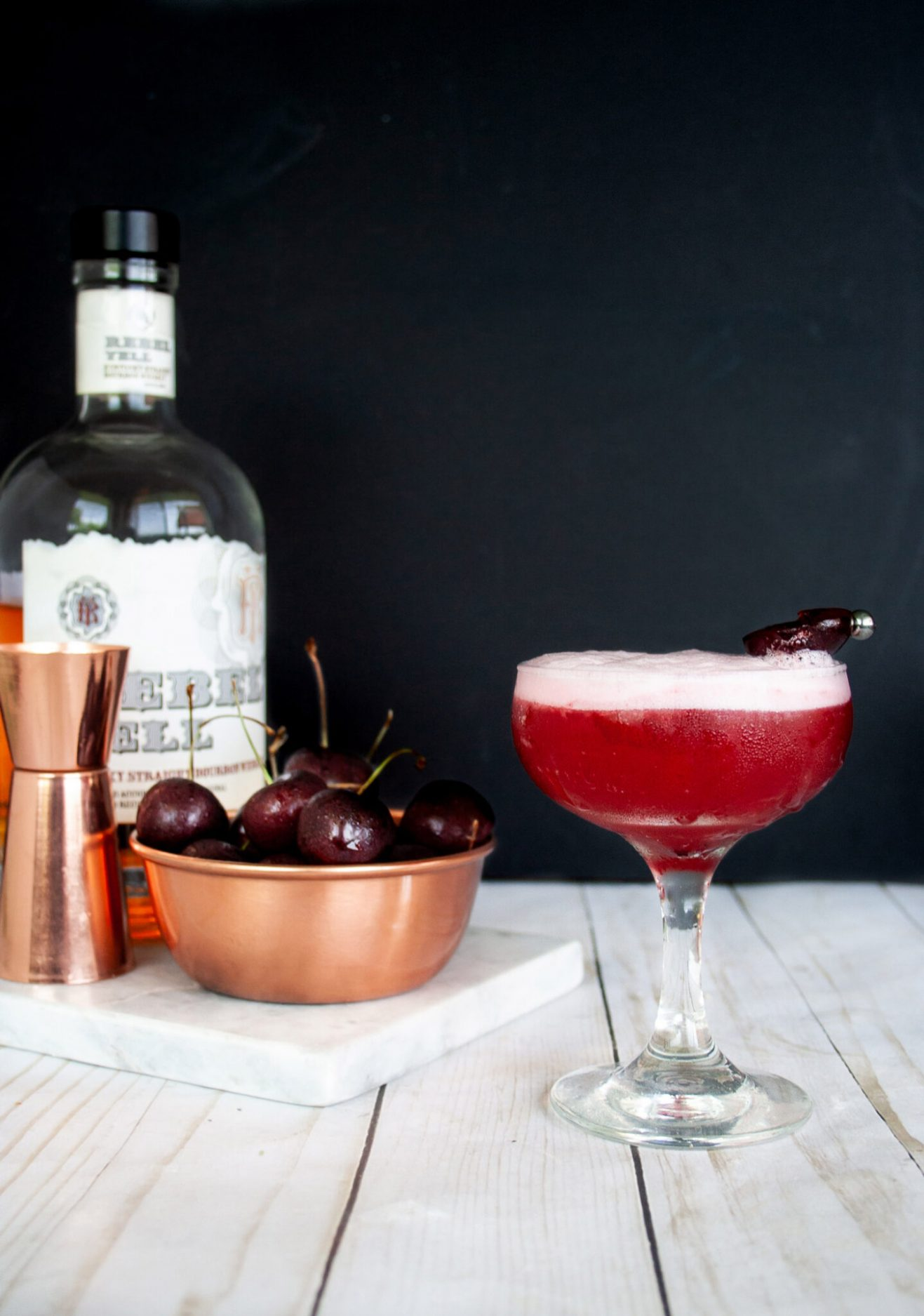 It's cherry season which means it's cherry cocktail time! Grab this Cherry Bourbon Sour recipe made with fresh cherries for a tart and slightly sweet spin on the classic Whiskey Sour. Pink cocktail and bourbon cocktail. Elle Talk | #cocktail #cocktailrecipe #drinkrecipe #drinks #recipeoftheday #cherries #easyrecipe #bourbon