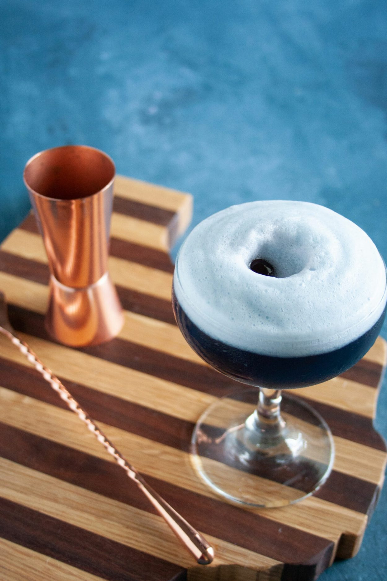 A cherry and lime martini cocktail with an egg white foam head to resemble the clouds of a hurricane. Drop 2 Luxardo maraschino cherries down the center of the egg white foam to get the hurricane eye effect. | Elle Talk | #vodka #coupe #cocktail #cocktailrecipe #drinkrecipe #recipeoftheday