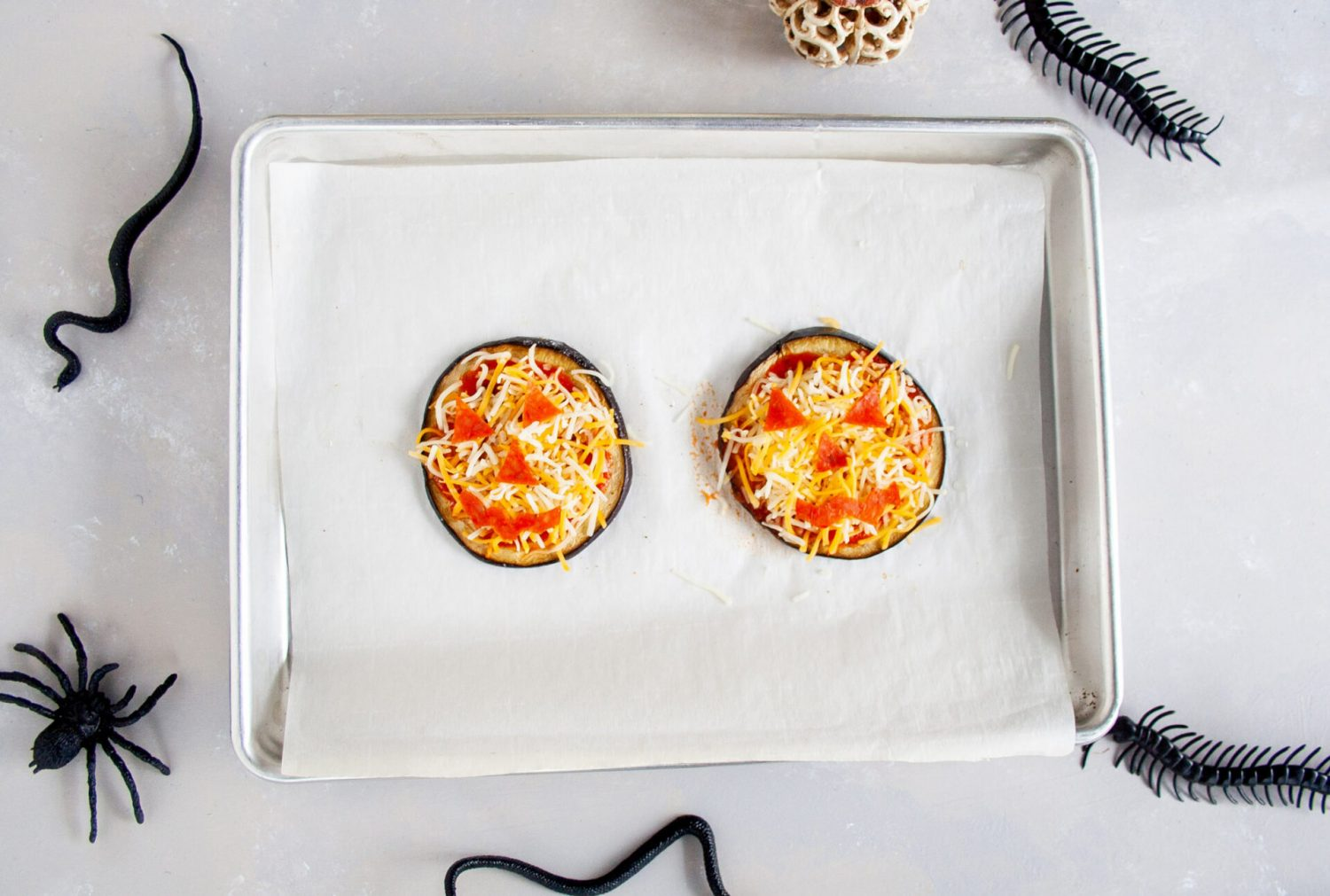 Halloween Eggplant Pizzas. These pepperoni and cheese pizzas that sort of look like pumpkins are delicious and easy to bake. They just might look more terrifying than you excepted. #ElleTalk #Pizza #Halloween