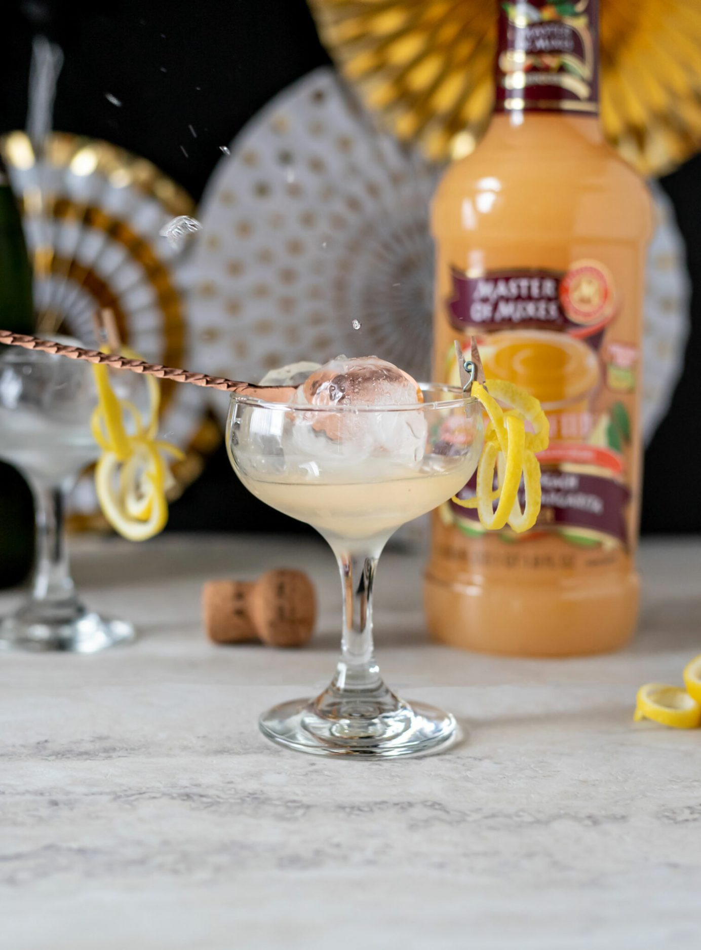 The Ball Drop is a New Years Eve ice ball cocktail made with strawberry vodka, Master of Mixes White Peach Margarita/DaiquiriMix, lemon juice, and edible glitter. Ice ball cocktail with Master of Mixes. #Sponsored #MasterofMixes #CocktailRecipe #Cocktail #NewYearsEve #ElleTalk