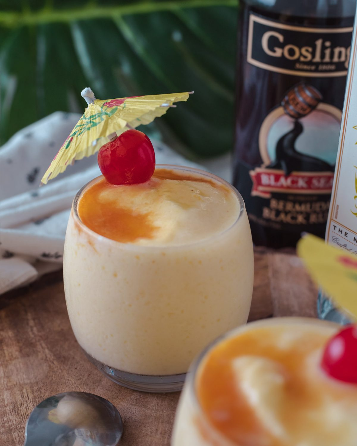 Our classic piña colada recipes made with white rum and black rum with delicious notes of coconut and fresh pineapple. It's a perfectly smooth and creamy frozen cocktail! #ElleTalk #cocktailrecipe #cocktails #rum #whiterum #darkrum #blackrum #rumcocktail #pinacolada #drinkrecipe