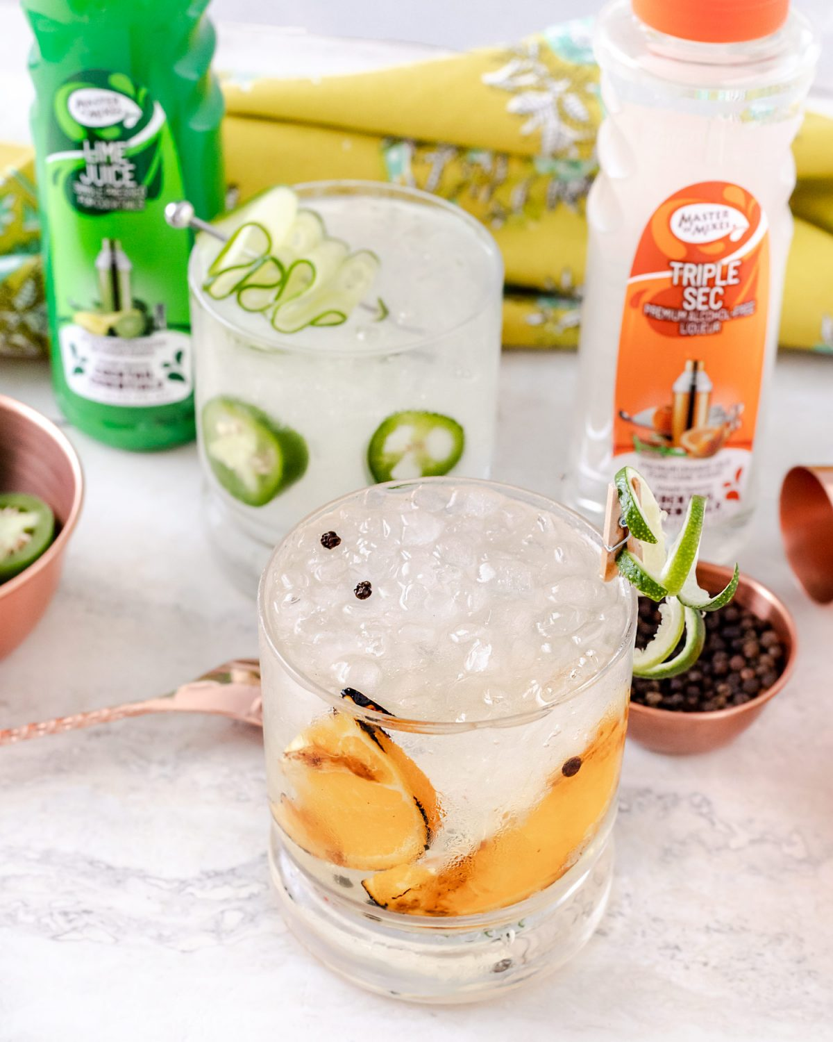 Gin & Tonic two different ways, one as a Jalapeño Cucumber Gin & Tonic and the other Smoked Sweet Orange and Peppercorn Gin & Tonic. These are the perfect spring cocktail recipes and are easy to make thanks to Master of Mixes Cocktail Essentials! #sponsored #ElleTalk #MasterofMixes #CocktailRecipe #DrinkRecipe #Gin #GinCocktail