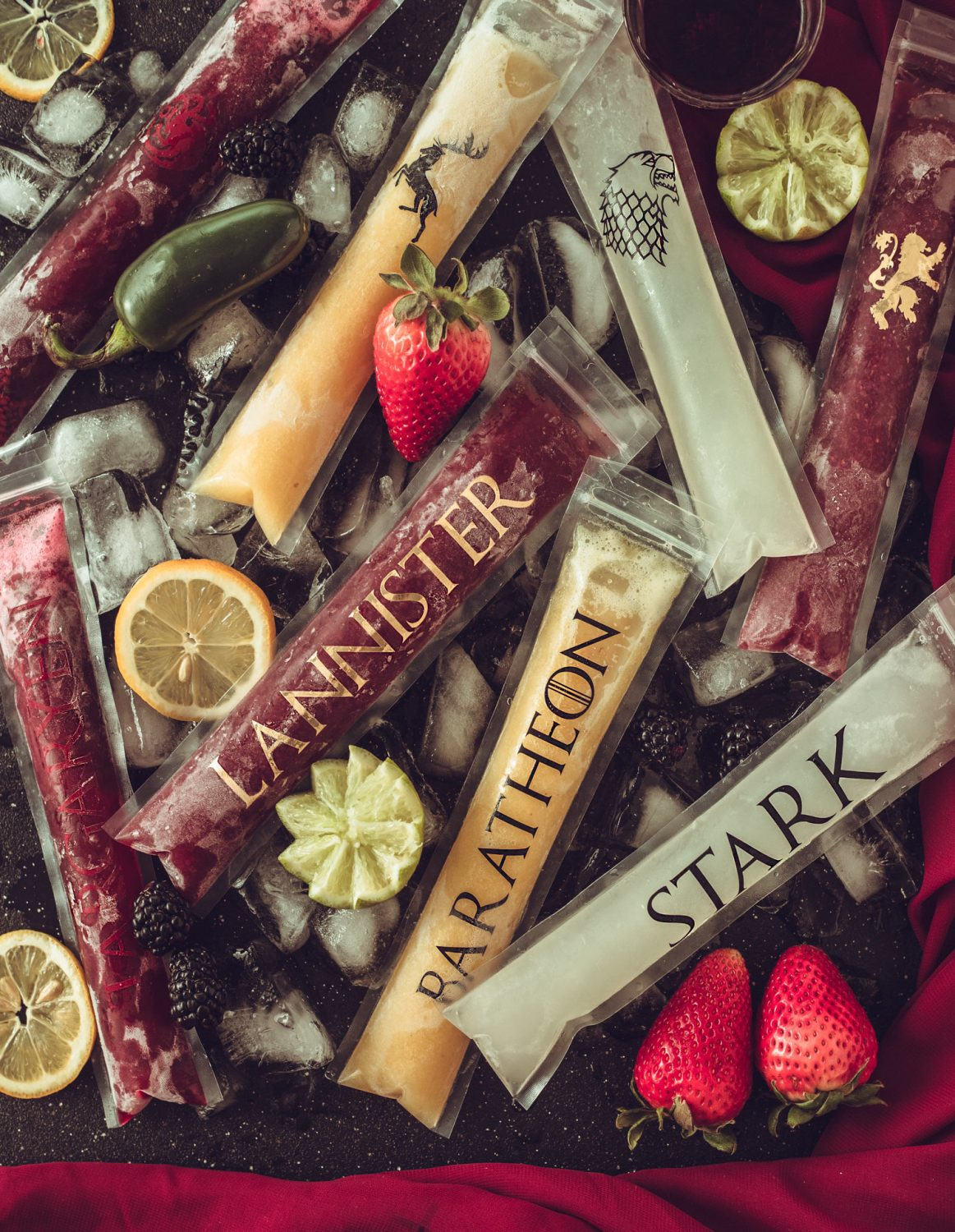 4 Game of Thrones boozy popsicles each representing the core houses of the show. Including Lannister Sangria Popsicles, Stark Moscow Mule Popsicles, Targaryen Spicy Whiskey Smash Popsicles, and Baratheon Piña Colada Popsicles. A perfect boozy treat for a Game of Thrones party! #ElleTalk #GameofThrones #GameofThronesParty #BoozyPopsicles #Popsicles #CocktailRecipe #Cocktail