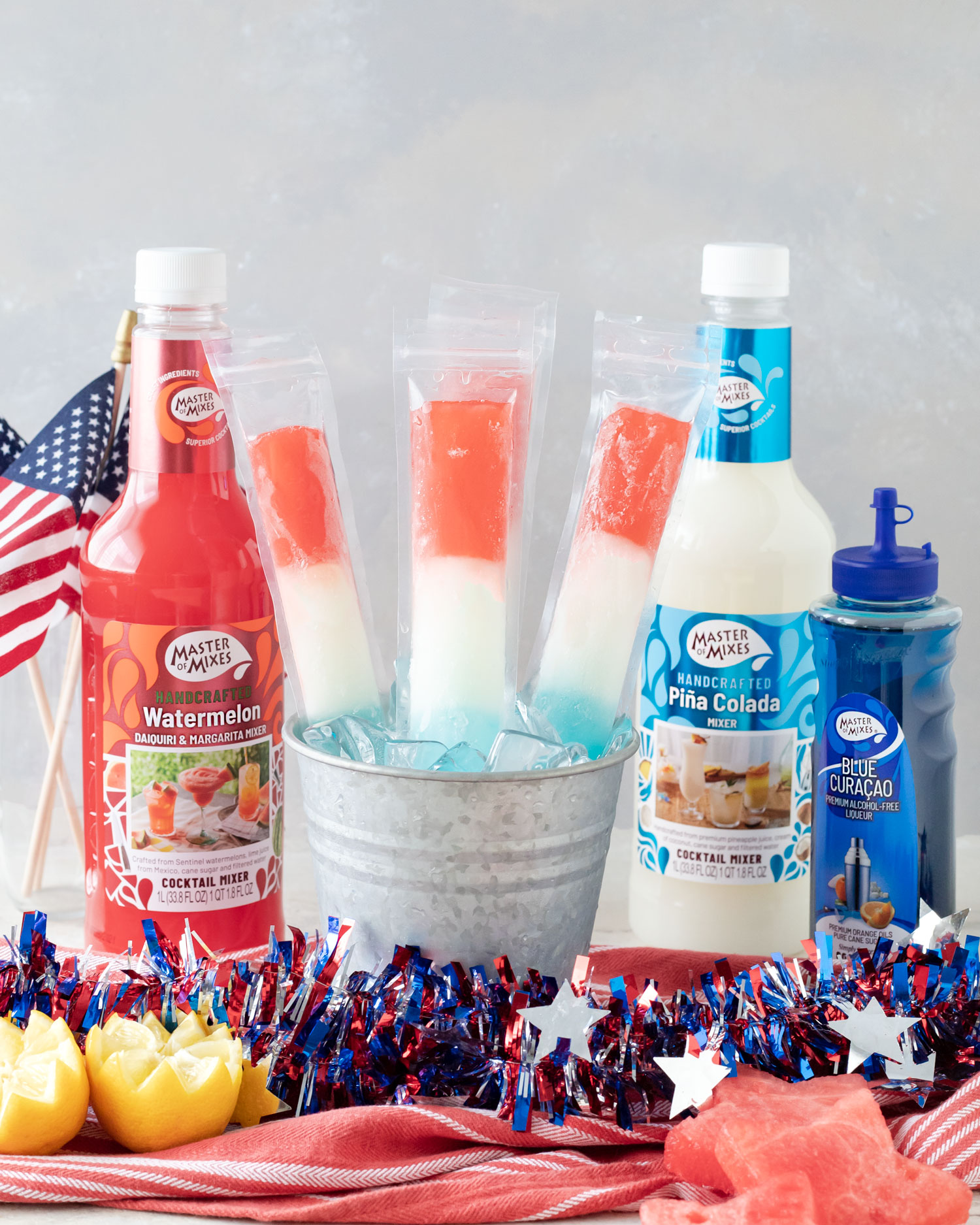 Red, White, and Blue themed boozy rum popsicles for summer using Master of Mixes to create a layered treat for Memorial Day, Fourth of July boozy popsicle treat, or Labor Day treat idea. #sponsored #CocktailRecipes #ElleTalk #MasterofMixes #BoozyPopsicles #Popsicles #IcePops #MemorialDayParty #FourthofJulyParty #LaborDayParty #RedWhiteandBlue