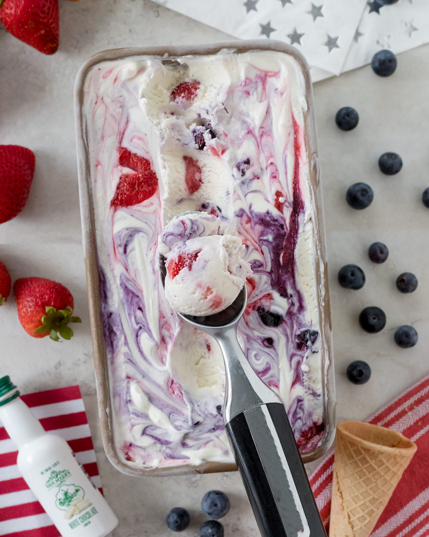 This Fourth of July no-churn ice cream is a white chocolate liqueur ice cream with strawberry and blueberry swirls that doesn't require an ice cream maker for a red, white, and blue dessert you'll love. This boozy no-churn ice cream recipe is super simple. #NoChurnIceCream #IceCreamRecipe #BoozyTreat #BoozyIceCream #HomemadeRecipe #HomemadeIceCream #DessertRecipe #FourthofJulyParty #FourthofJulyIceCream #ElleTalk