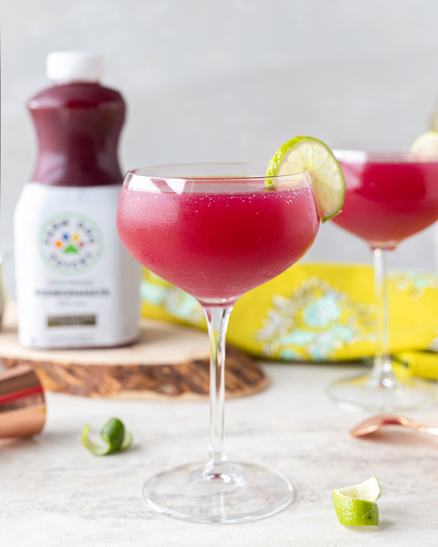 Pomegranate Gimlet mocktail made with Farm Dog Juices Pomegranate Juice that is now at H-E-B. This non-alcoholic cocktail recipe is tart and sweet for a drink that's perfect all year long. ElleTalk #spons #Mocktail #MocktailRecipe #CocktailRecipe #ZeroAlcohol #LowABV #nonalcoholic