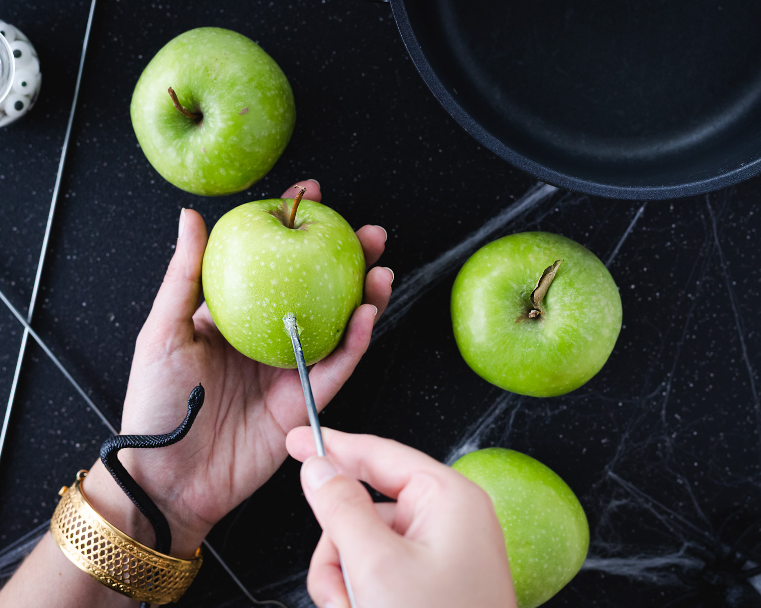 Candy apples that have been soaked in alcohol for a boozy adult Halloween treat that will be sure to bewitch your guests. These apples are dipped in a black and edible glitter purple candy coating. #ElleTalk ElleTalk #Halloween #HalloweenRecipe #AppleRecipe #BoozyRecipe #BoozyTreat #ApplePucker #CandyApple