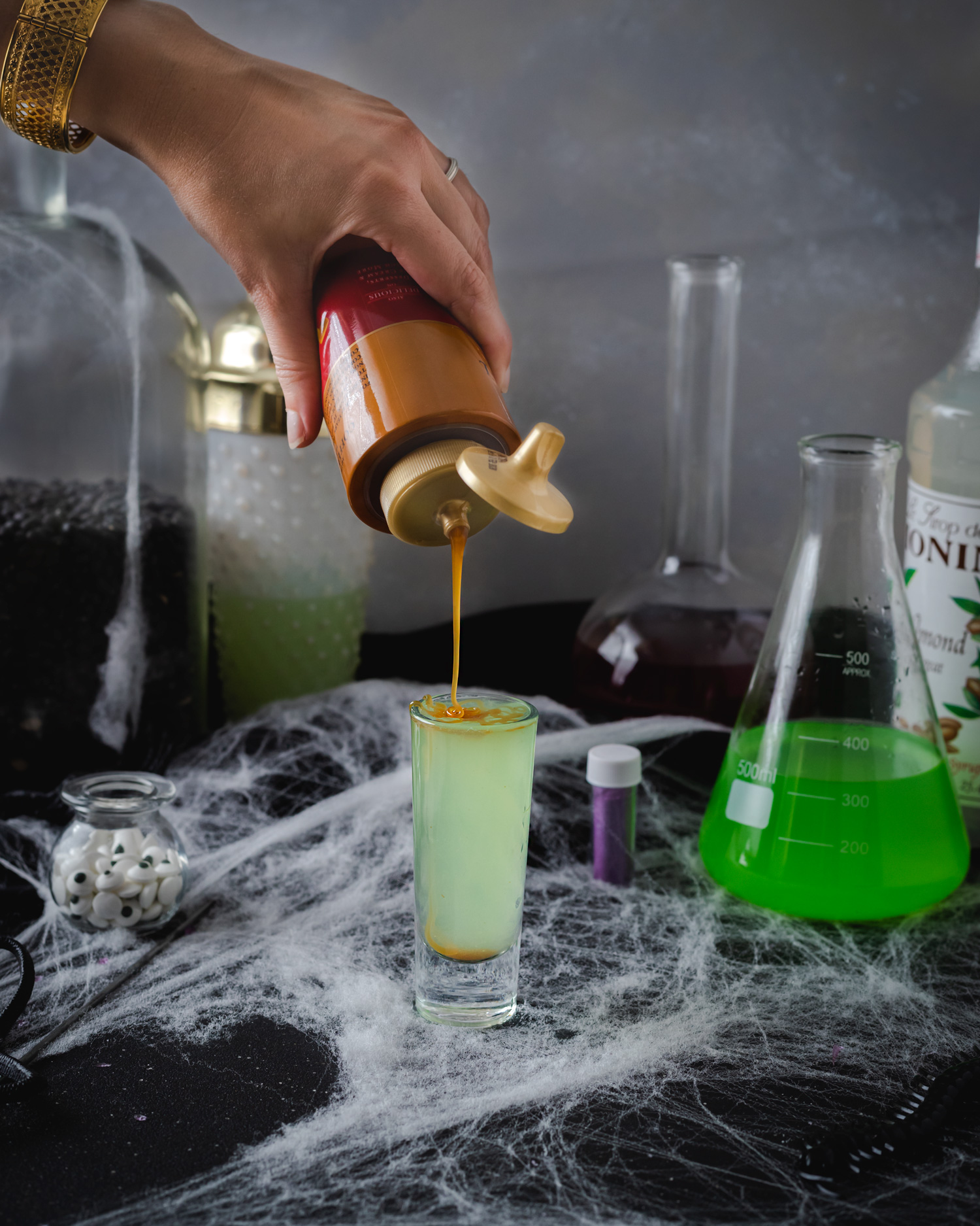 Bright green Halloween shot that tastes like caramel apples with almonds. Apple pucker, spiced rum, orgeat syrup, and caramel shot recipe for Halloween. #ElleTalk #Halloween #HalloweenRecipe #ShotRecipe #ApplePucker #SpicedRum #Caramel #Orgeat #CocktailRecipe